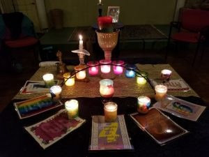 An altar table arrayed with cards representing each of the 7 UU principles and lit candles in a rainbow of colors.